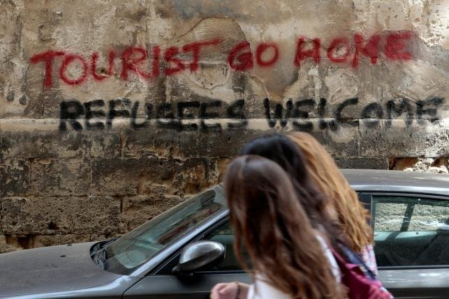 People walk past a graffiti in Palma de Mallorca, in the Spanish island of Mallorca, May 23, 2016. REUTERS/Enrique Calvo